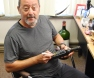 Jean Reno signs bottles of his olive oil in Ariane's office.